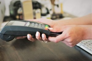 hands holding credit card and card reader