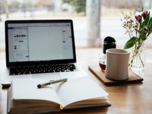 a pen sits on a laptop in front of an open laptop and a cup of coffee
