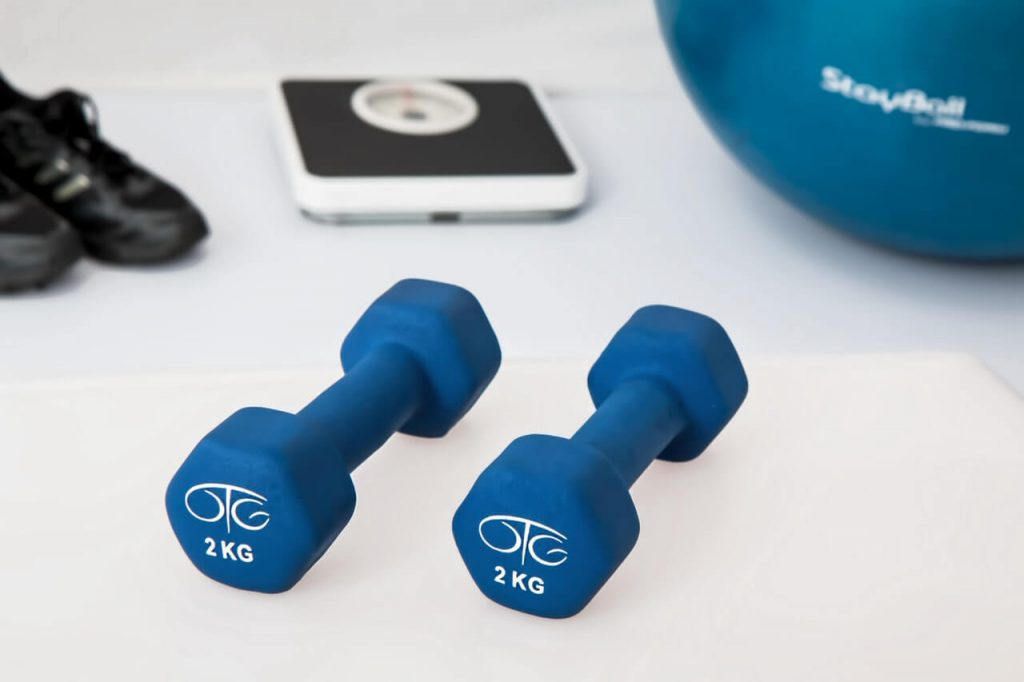 dumbbells and assorted fitness gear on a white floor