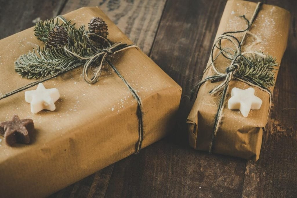 two brown wrapped christmas presents on a wooden table